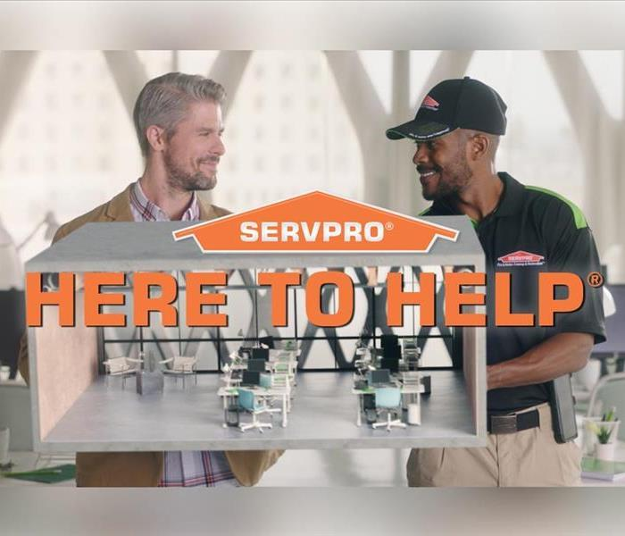 A SERVPRO employee smiling with a customer who is happy with completed work.