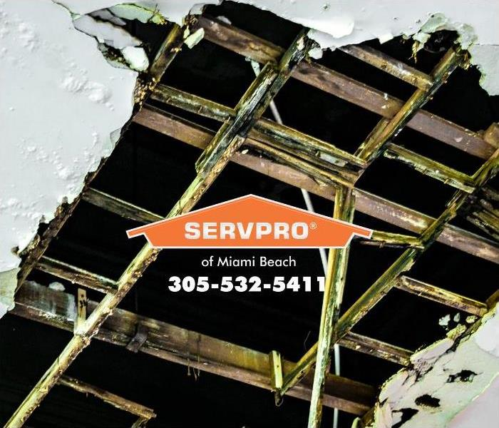 A large hole in the ceiling of a commercial building is water-damaged, showing leaking pipes and damaged structures.